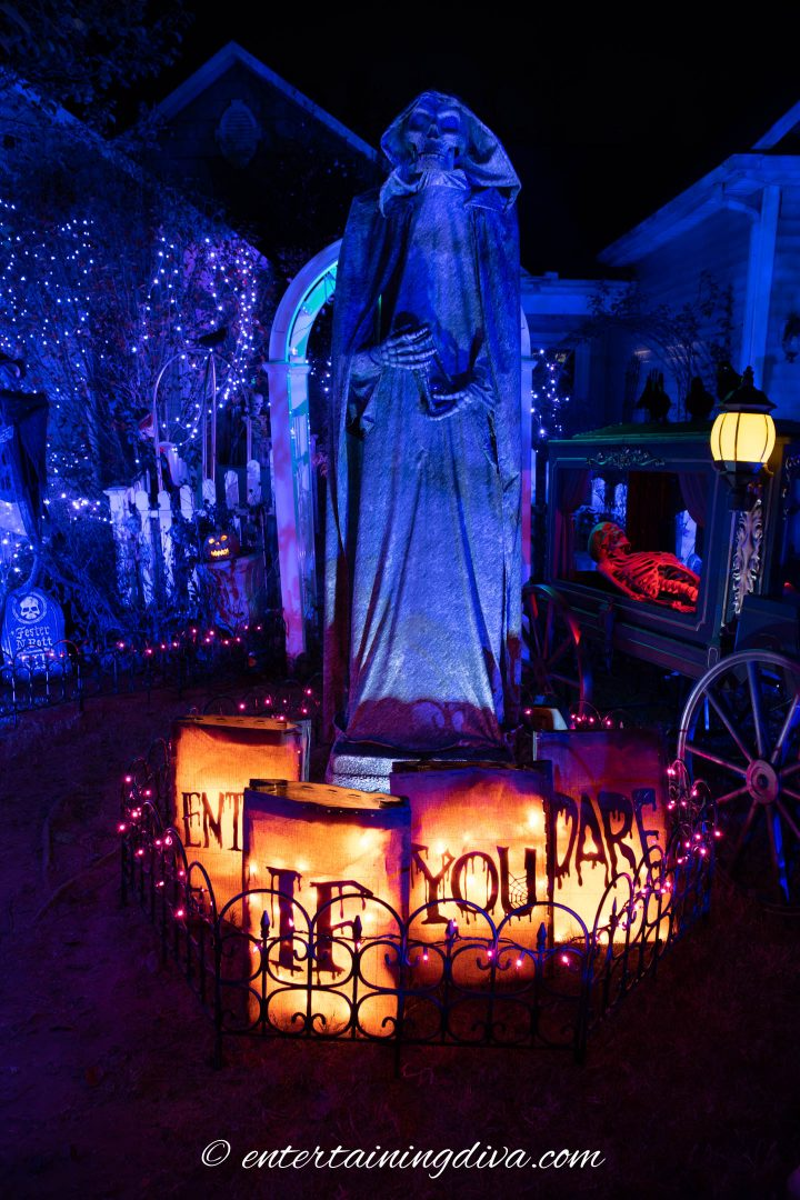 Large Halloween grim reaper statue lit up at night