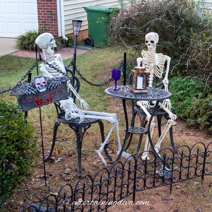 Skeletons sitting at an outdoor  table