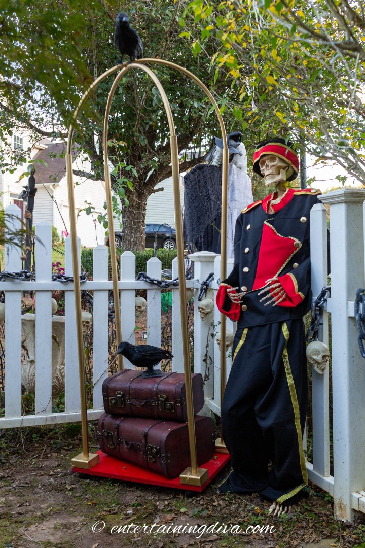 DIY luggage cart with suitcases and a skeleton wearing a bell boy costume