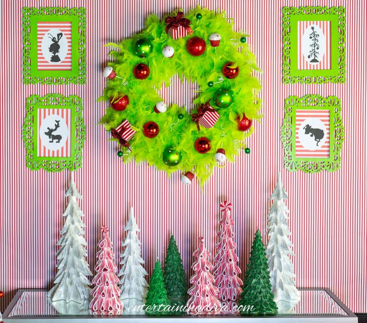 The DIY Grinch printable silhouette pictures hung on either side of a Grinch wreath.