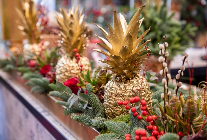 DIY Christmas centerpiece made with pineapples painted gold, evergreens, pussy willows and red berries ©vikakurylo81 - stock.adobe.com