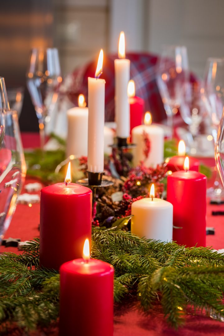 DIY Christmas centerpiece made from red and white candles with evergreens and red berries
