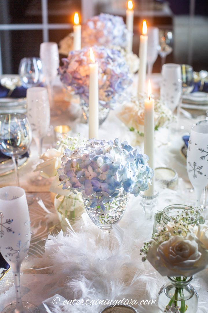Wintry centerpiece made with white feather boas, blue and white flowers and white candles