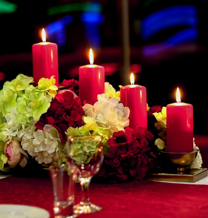 DIY Christmas centerpiece made of red and white faux hydrangeas with red pillar candles