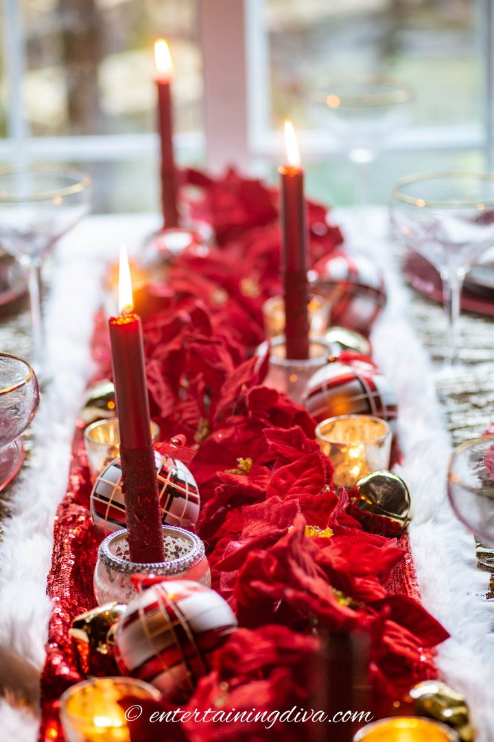 Table-length DIY Christmas centerpiece made with a poinsettia garland, red candles and Christmas ornaments