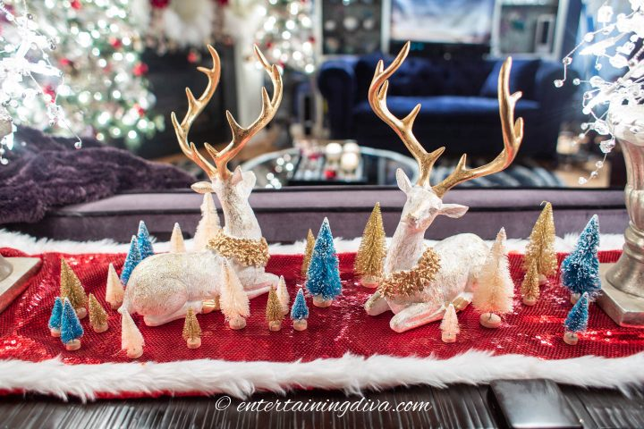 Christmas centerpiece made with a red runner, bottlebrush trees and deer Christmas decorations