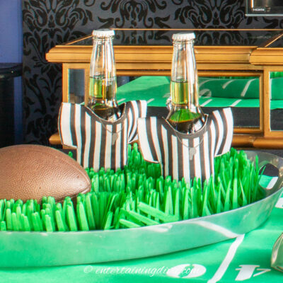 A football and two beer bottles in referee koozies on a football field tray