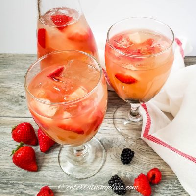 two glasses and a pitcher filled with sangria and berries