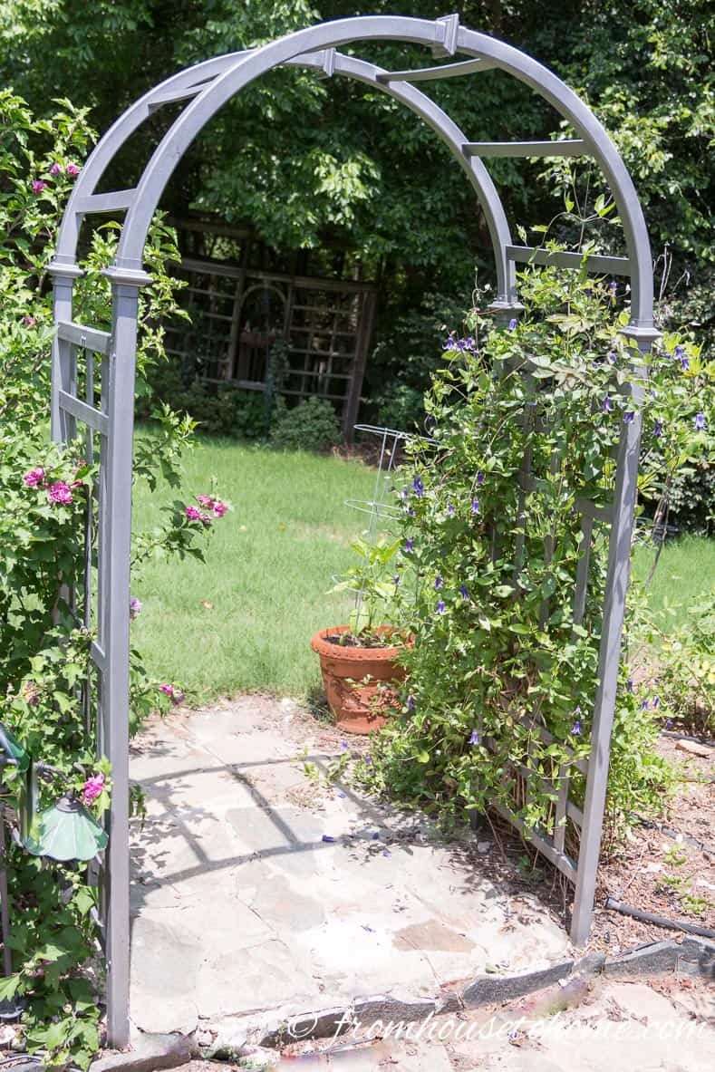 This arbor was originally white plastic...a little spray paint makes it look like metal | 10 Tips For Creating A Low Maintenance Garden