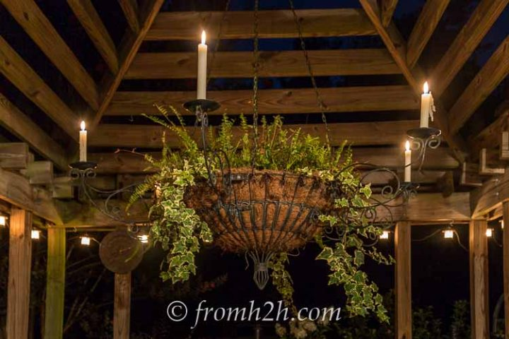 A candelabra hung under a gazebo at night