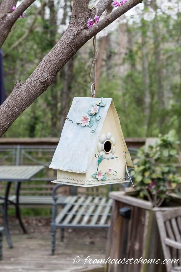 Decorated birdhouse hung from a tree in the garden