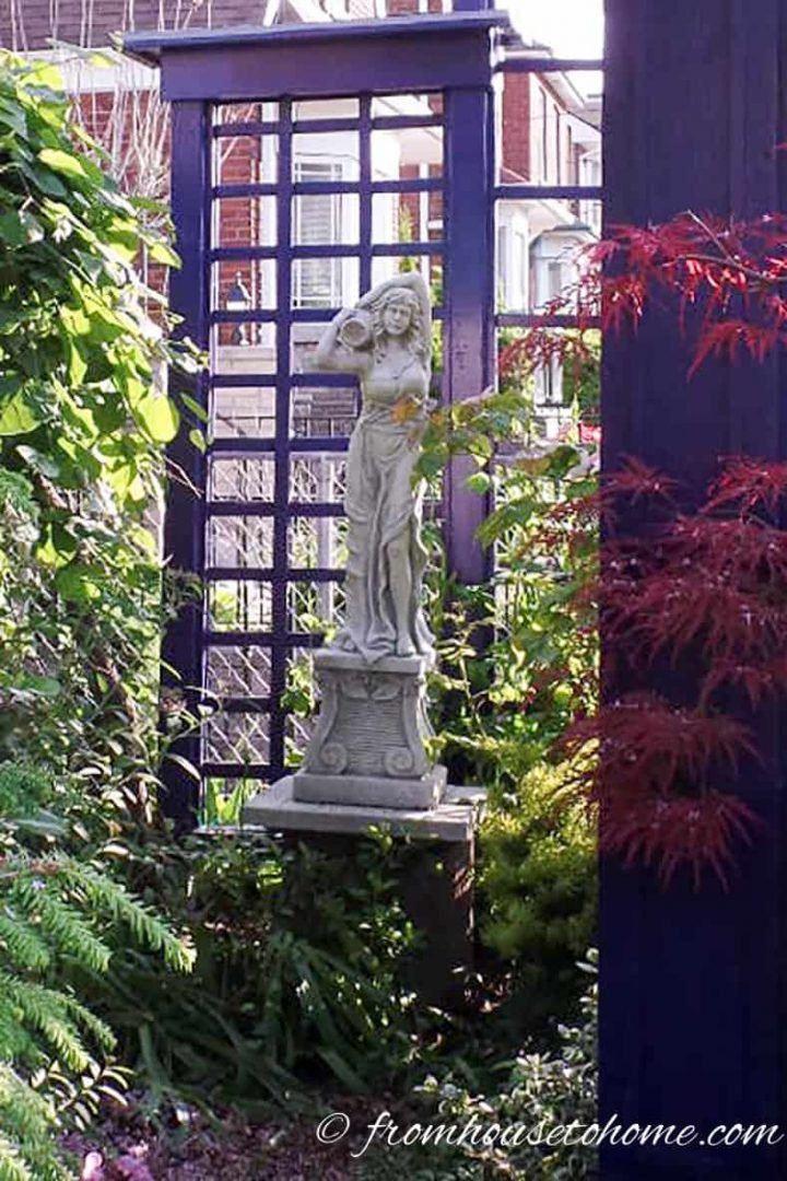 Garden statue in front of a blue fence