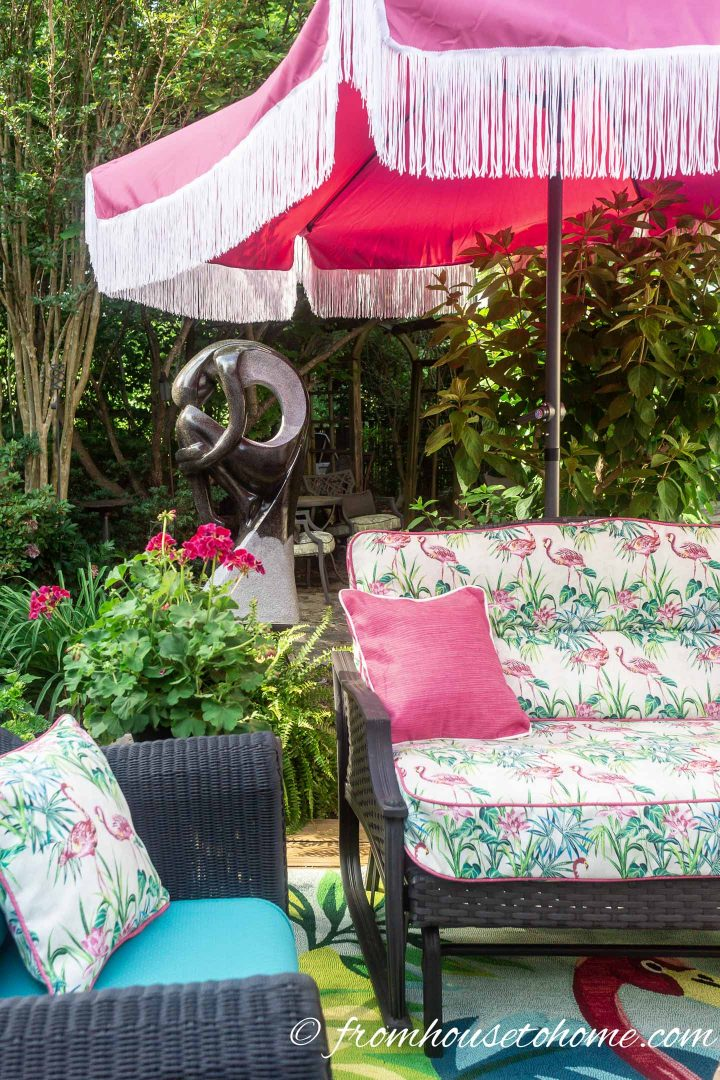 Patio umbrella with fringe over an outdoor sofa and chair