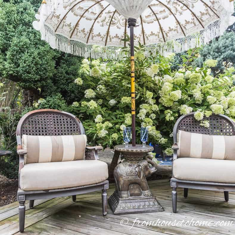 Plants and an umbrella over chairs create a secret garden
