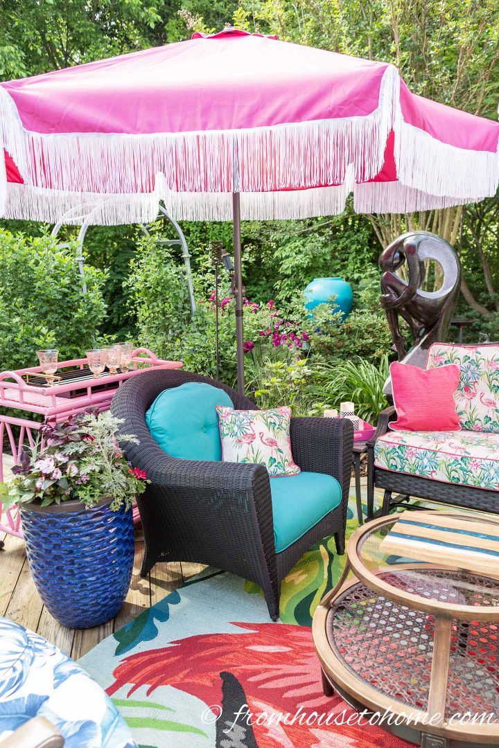 Pink umbrella with white fringe over a large outdoor arm chair