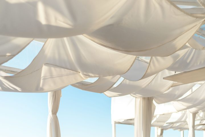White shade sails hung loosely from a pergola