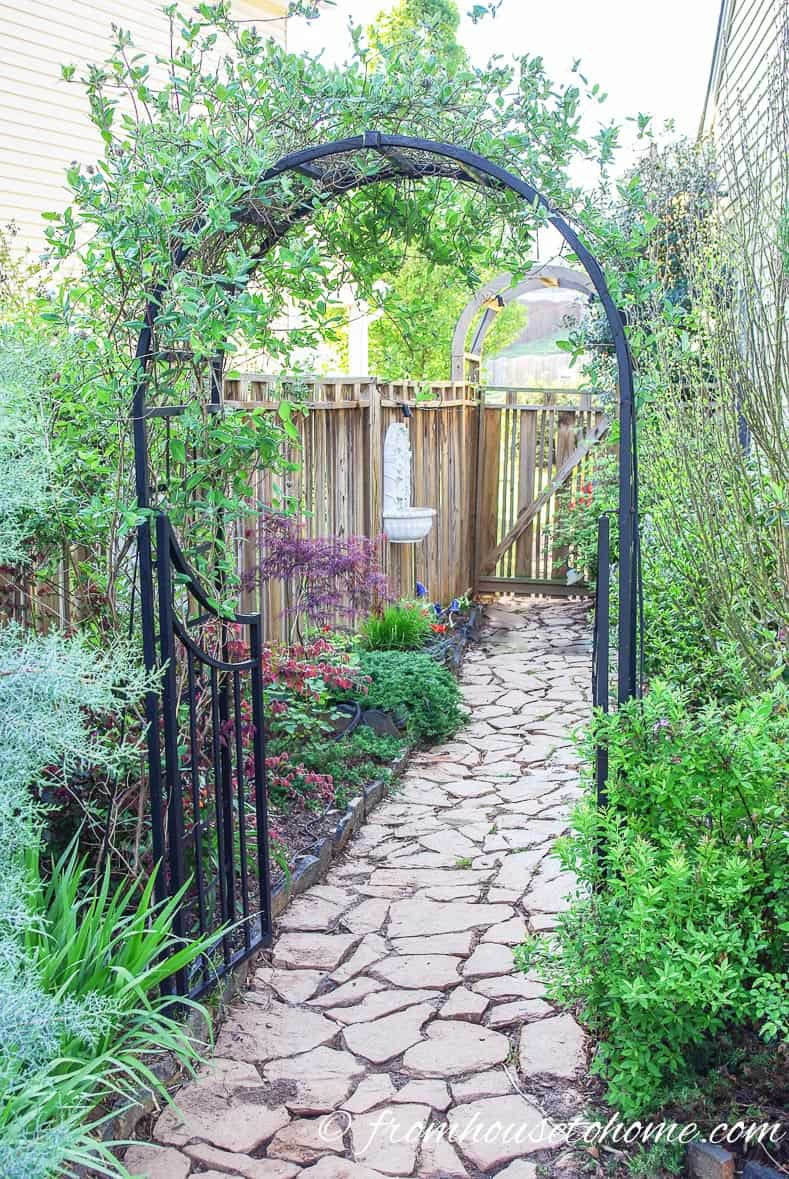 Wrought iron arbor over a backyard secret garden pathway