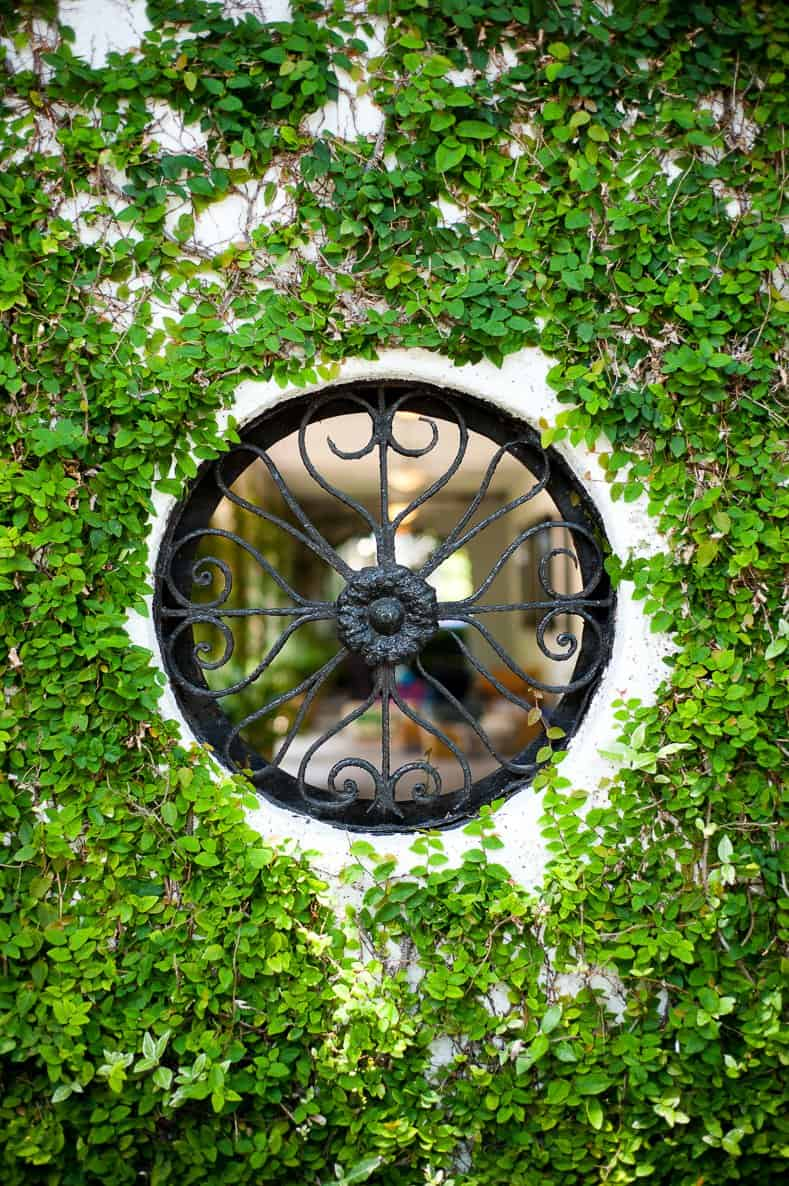 Round wrought iron window looking into a private garden ©Heather Wissman - stock.adobe.com