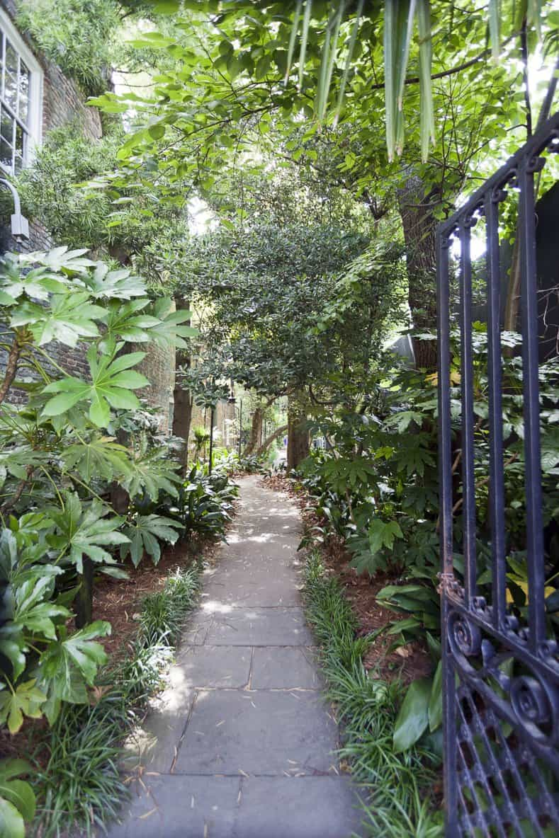 Gated alley entrance to secret garden with curved pathway. Charleston, South Carolina. ©Noel - stock.adobe.com