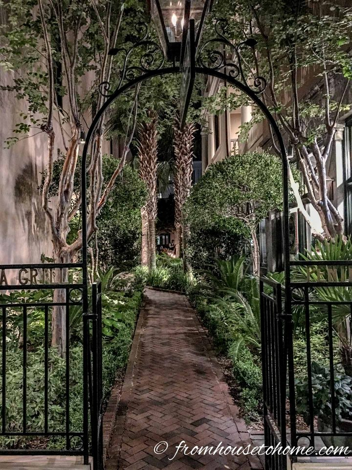 An arbor leading into a secret garden lit up at night