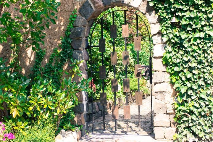 Arched metal door as garden gate