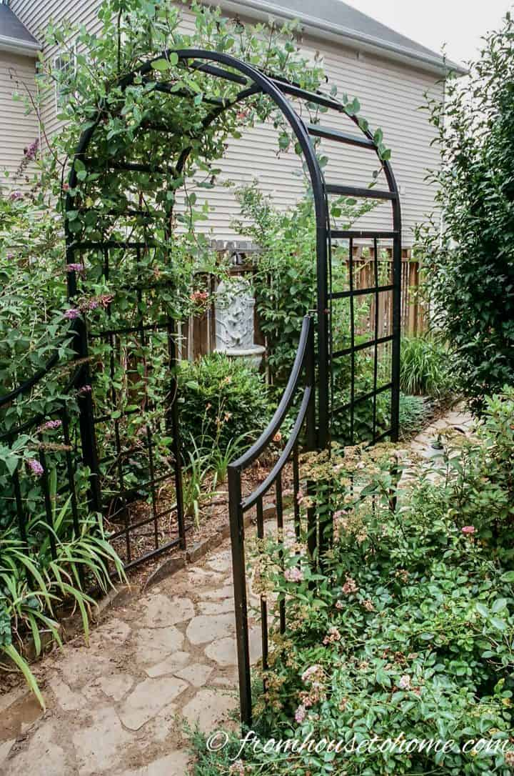 Black arched arbor with garden gate