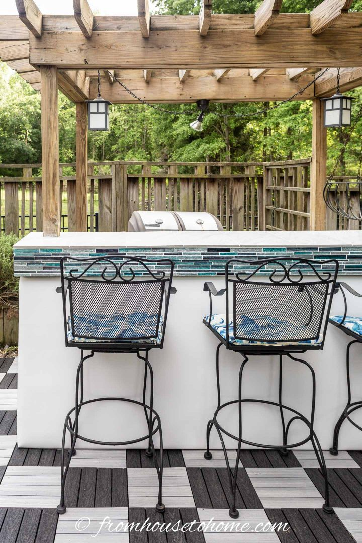 Tiled outdoor bar with a white faux leather front and a pergola