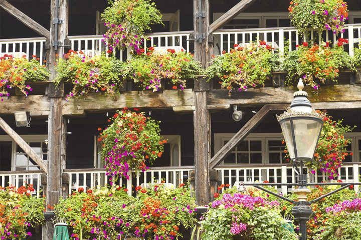 Traditional hanging baskets and window boxes on front porch