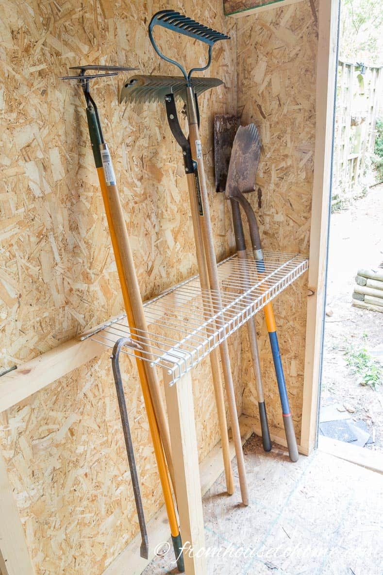 Wire shelves for garden tool storage like rakes and shovels