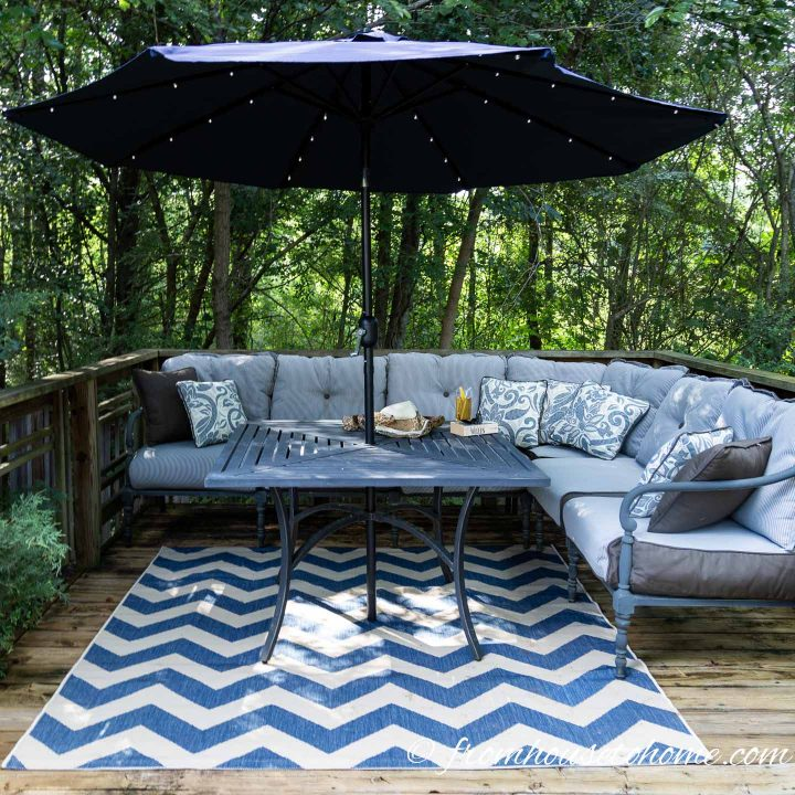 Deck decorated with a blue and white area rug, blue and white cushions and a blue umbrella