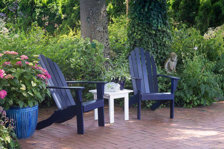 Blue Adirondack chairs with a white table on a patio ©Jamie Hooper - stock.adobe.com
