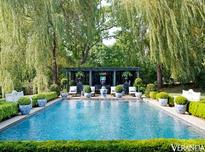 Blue and white ginger jars around a pool by Carolyne Roehm, via Veranda