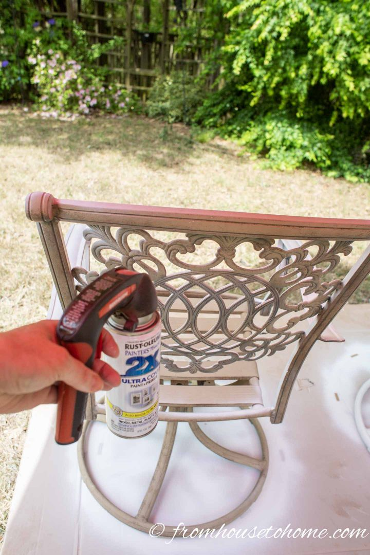 The back of a metal patio chair being spray painted