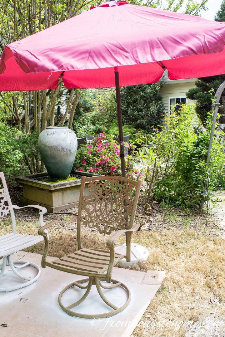 A beige metal outdoor chair under the shade of an umbrella