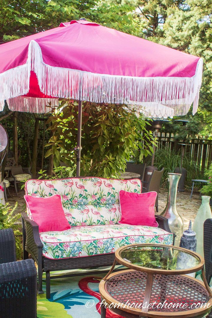 Pink patio umbrella over an outdoor sofa on a deck