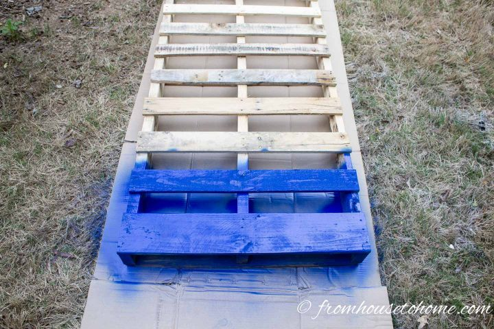 Bottom two slats of a pallet painted blue