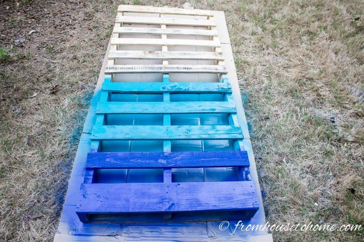 Bottom slats of a pallet painted in two colors of blue