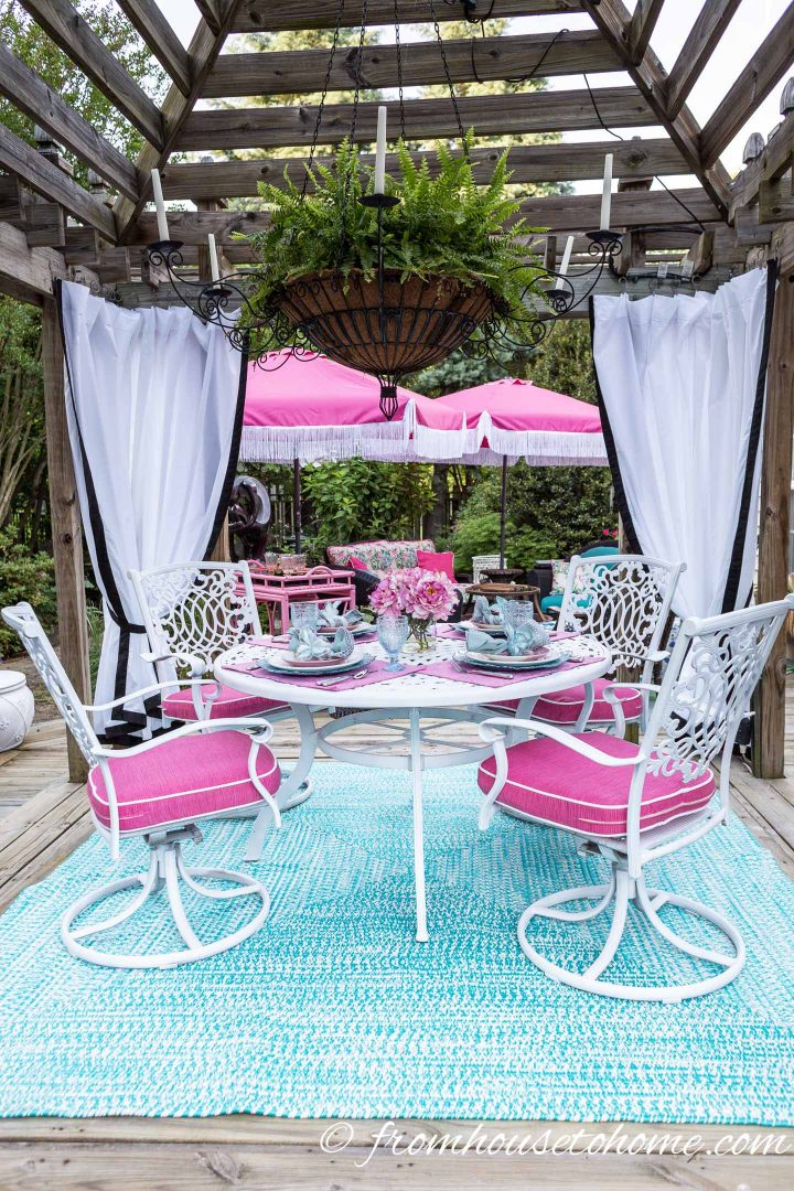 Gazebo with curtains and a pink and turquoise table setting