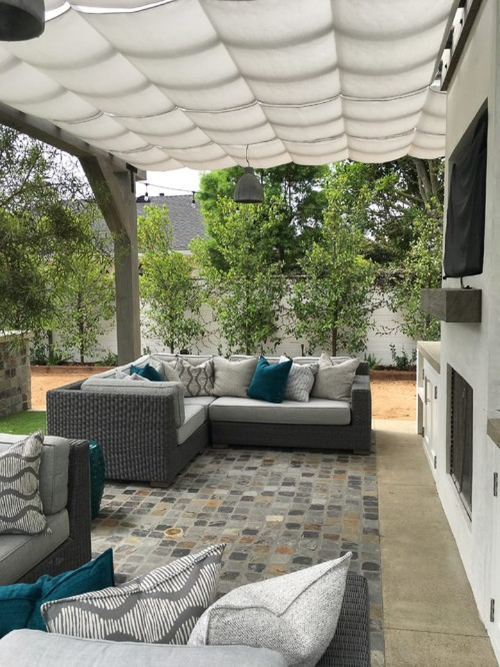 White canvas canopy as a pergola cover over a stone patio