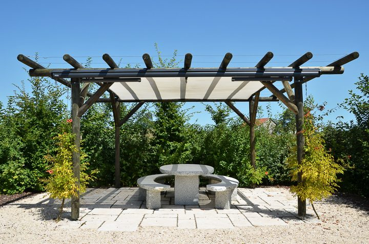 Pergola with a shade sail installed under the beams