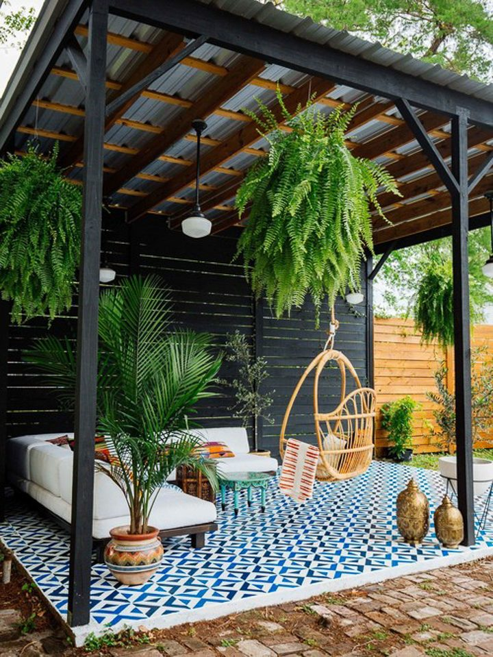 Pergola with a tin roof covering a blue and white patio