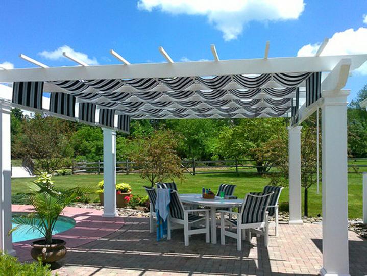 White pergola over brick patio with white and blue striped fabric pergola cover