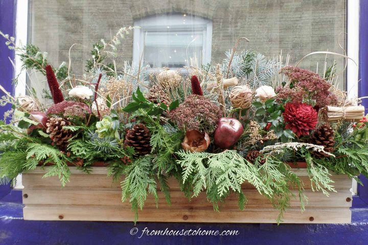 Winter window box with evergreens, pine cones and twigs