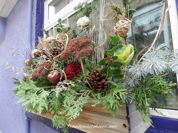 A winter window box filled with evergreens, dried flowers, pine cones and faux apple picks
