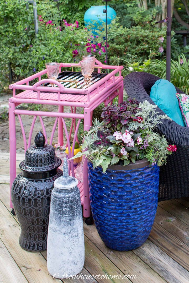 Outdoor bar cart, large vases and a blue container on a deck