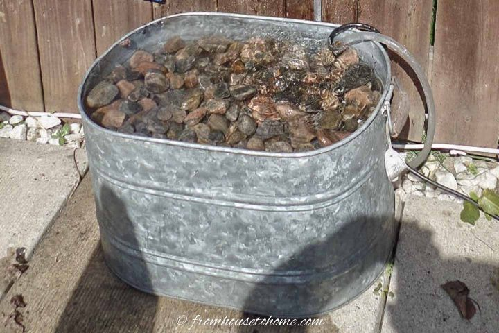 Galvanized tub filled with rocks as the bottom of a fountain