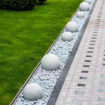 modern gravel garden edging with round concrete balls down the middle