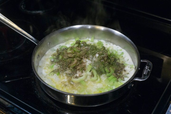 Celery, onions and spices being cooked in butter in a saute pan