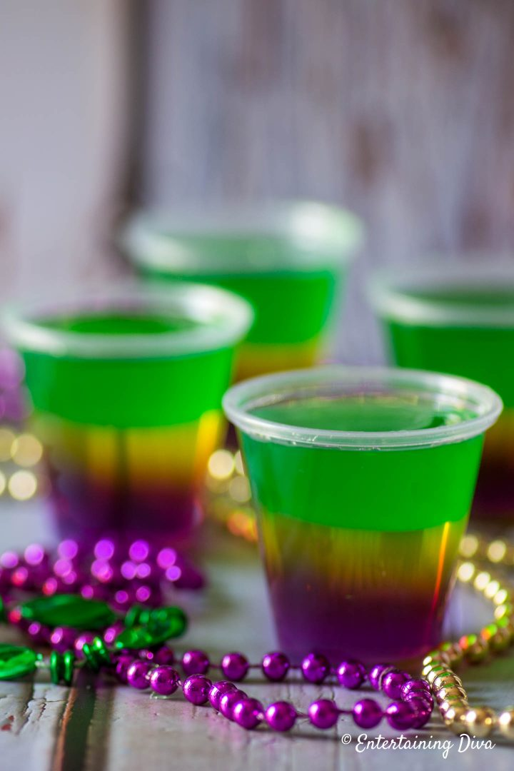 Layered Mardi Gras jello shots with Mardi Gras beads