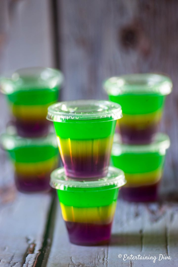 Purple, gold and green Mardi Gras jello shots in jello shot cups with lids